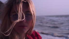 A beautiful girl with long blond hair, in a red T-shirt, in unusual, rectangular, purple glasses is looking into the stock video