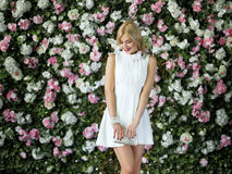 Beautiful girl with long blonde hair posing against floral background. Royalty Free Stock Images