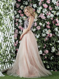 Beautiful girl with long blonde hair posing against floral background. Royalty Free Stock Photography
