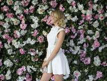 Beautiful girl with long blonde hair posing against floral background. Royalty Free Stock Photos