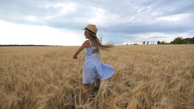 Beautiful girl with long blonde hair running through wheat field, turning to camera and smiling. Cute happy child in