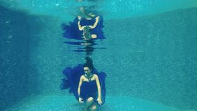 Beautiful girl in long blue dress poses for camera underwater in pool stock video