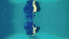 Beautiful girl in long blue dress swims under water in swimming pool. Underwater. Beautiful brunette in long blue dress dives under water in swimming pool stock video footage