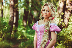 Beautiful girl with a long braid in pink lace dress smiles in the forest. Beautiful young woman with long hair, twisted into a braid, walking and laughing in Stock Images