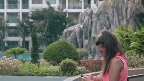 Beautiful girl relaxes outside and chats with friends. Beautiful girl with long brown ponytail and in bright top relaxes outside and chats with friends on phone stock video