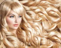 Beautiful girl with long curly blond hair stock photos