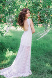 Beautiful girl with long curly hair in a white dress in the summer park Royalty Free Stock Photography