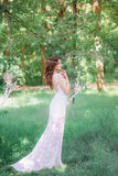 Beautiful girl with long curly hair in a white dress in the summer park Stock Image