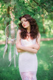 Beautiful girl with long curly hair in a white dress in the summer park Royalty Free Stock Photo