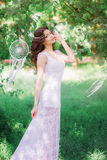 Beautiful girl with long curly hair in a white dress in the summer park Royalty Free Stock Images