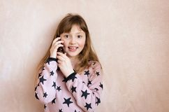 Little girl is talking on a mobile phone. Beautiful girl with long dark blonde hair and wonderful expressive brown eyes with smartphone. A little girl is Royalty Free Stock Image