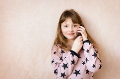 Little girl is talking on a mobile phone royalty free stock images