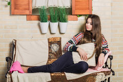 Beautiful girl with long dark hair sitting on a bench near the house under the window Royalty Free Stock Photos