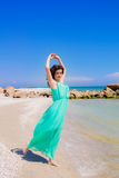 Beautiful girl in a long dress dancing on the beach Royalty Free Stock Image