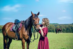 A beautiful girl in a long dress and horse. A beautiful girl in a long burgundy dress is standing in the field and holding a brown horse under the knots. Far stock photo
