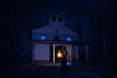 Beautiful girl in long dress with lantern alone in the dark forest Royalty Free Stock Photos