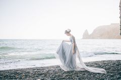Beautiful girl in a long dress with a veil on the beach, summer,. Rocks Stock Photography