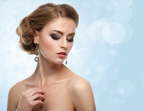 Beautiful girl with long earrings. Smokey make-up. Blue background with bokeh Royalty Free Stock Photos
