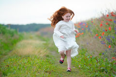 Beautiful girl with long golden hair running toward funny smilin Royalty Free Stock Photo