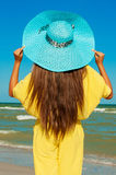 Beautiful girl with long hair on the beach in a blue hat Royalty Free Stock Photos
