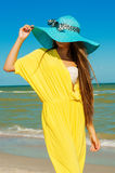 Beautiful girl with long hair on the beach in a blue hat Royalty Free Stock Photography