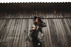 Beautiful girl with long hair and black hat, stands on the background of vintage old wooden house stock photo
