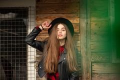 Beautiful girl with long hair and black hat, stands on the background of vintage old wooden house stock images