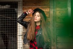 Beautiful girl with long hair and black hat, stands on the background of vintage old wooden house royalty free stock photography