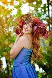 Beautiful girl with long hair in blue dress, in a wreath of red and green leaves standing against bright fall bushes royalty free stock image