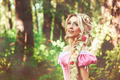 Beautiful girl with long hair braided in a braid, in corset and magnificent pink dress. Beautiful young woman with long hair, twisted into a braid, walks in the Stock Photos