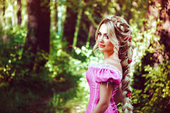 Beautiful girl with long hair braided in a braid, in corset and magnificent pink dress. Beautiful young woman with long hair, twisted into a braid, walks in the Royalty Free Stock Photography