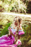 Beautiful girl with long hair braided in a braid sitting by the lake and admire the flower. Beautiful girl with long hair braided in a braid looks at a flower Royalty Free Stock Photography