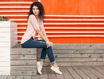 Beautiful girl with long hair brunette in jeans sits near wall of orange old white wooden planks Stock Images