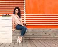 Beautiful girl with long hair brunette in jeans sits near wall of orange old white wooden planks Stock Photos