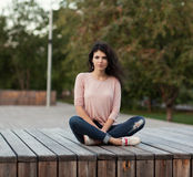 Beautiful girl with long hair brunette in jeans sits on wooden planks Stock Photography