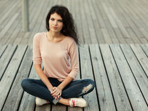 Beautiful girl with long hair brunette in jeans sits on wooden planks Royalty Free Stock Image