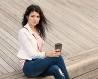 Beautiful girl with long hair brunette in jeans standing on old wooden planks with a cup of coffee in hand  on a warm summer Royalty Free Stock Photos