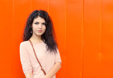 Beautiful girl with long hair brunette standing near background orange wall Stock Image