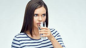 Beautiful girl with long hair drinking water from glass. Isolated portrait Stock Images