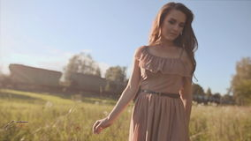 Beautiful girl with long hair goes in a green meadow, and touch the flowers.To whirl, to enjoy. In the background a. Train is passing. Shot in Full HD stock video footage