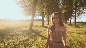 Beautiful girl with long hair goes on a green trail among the trees, circling and enjoying the sun and nature. Girl stock video footage
