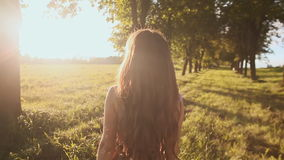 Beautiful girl with long hair goes on a green trail among the trees, circling and enjoying the sun and nature. stock video