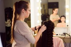 Beautiful girl with long hair, hairdresser weaves a French braid, in a beauty salon. Professional hair care and creating royalty free stock photos