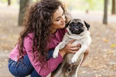 Pretty brunette girl walking with dog in the park. Animal concept. Beautiful girl with long hair having fun with doggie mops in the park outdoors. Young woman Royalty Free Stock Photo