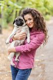 Pretty brunette girl walking with dog in the park. Animal concept. Beautiful girl with long hair having fun with doggie mops in the park outdoors. Young woman Stock Images