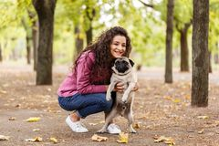 Pretty brunette girl walking with dog in the park. Animal concept. Beautiful girl with long hair having fun with doggie mops in the park outdoors. Young woman Stock Photos