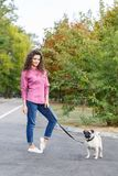 Pretty brunette girl walking with dog in the park. Animal concept. Beautiful girl with long hair having fun with doggie mops in the park outdoors. Young woman Royalty Free Stock Photography