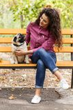 Pretty brunette girl walking with dog in the park. Animal concept. Beautiful girl with long hair having fun with doggie mops in the park. Young woman with puppy Stock Images
