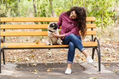 Pretty brunette girl walking with dog in the park. Animal concept. Beautiful girl with long hair having fun with doggie mops in the park. Young woman with puppy Royalty Free Stock Images