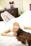 Beautiful girl with long hair laying in bed. Gorgeous young woman tired in bed smiling Royalty Free Stock Photo